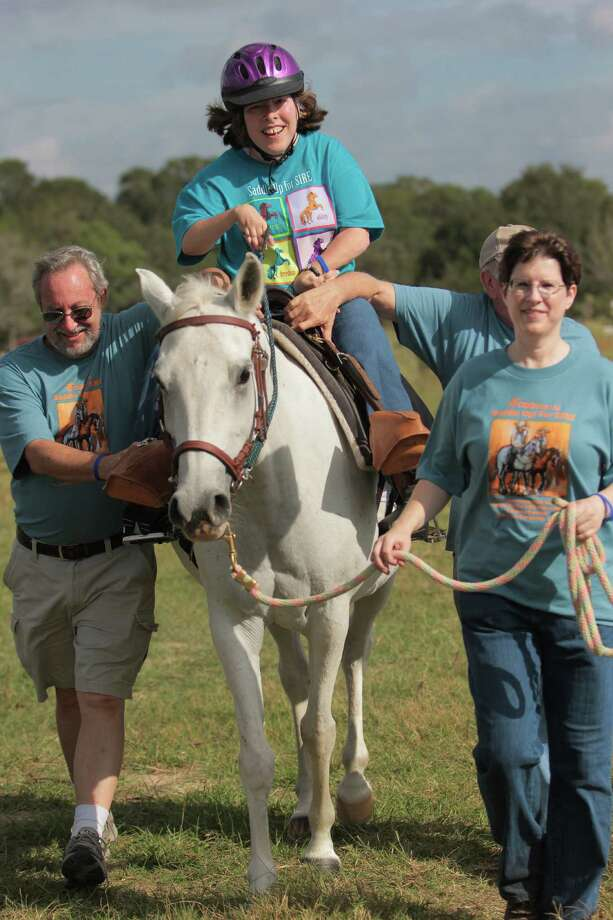 Julie Sparrow relishes the Saddle Up! for SIRE  Ride-a-Thon in Cat Spring, escorted by volunteers Keith O'Connor, from left, Kenneth Campbell and Holly Freeland. Photo: James Pharaon
