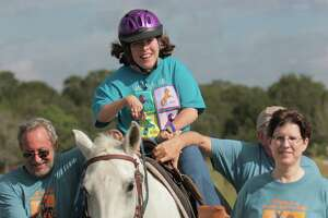 Julie Sparrow relishes the Saddle Up! for SIRE  Ride-a-Thon in Cat Spring, escorted by volunteers Keith O'Connor, from left, Kenneth Campbell and Holly Freeland.