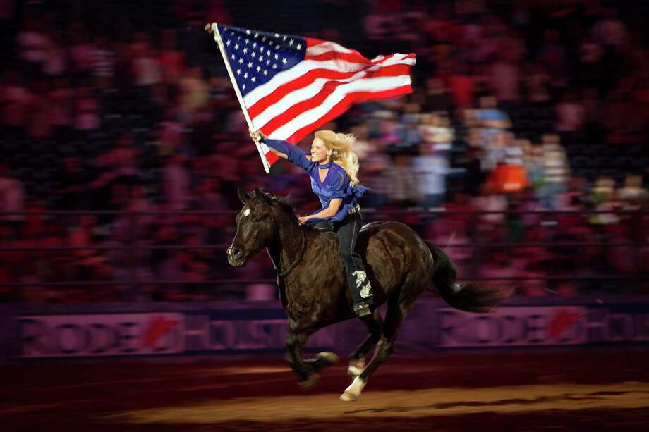The American flag is carried through the stadium on horseback during the playing of the national anthem at the Houston Livestock Show and Rodeo. Photo: Smiley N. Pool, Staff / © 2012  Houston Chronicle