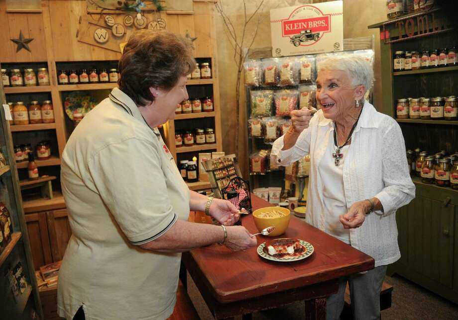 Ruth Dawson, right, of Kingwood, samples a Klein Bros. culinary creation served by  Margie Ferrington at Granny's Corner in Tomball. Ferrington worked 26 years with Klein's father at the supermarket. Now she does food demonstrations of the products. Photo: Jerry Baker, Freelance