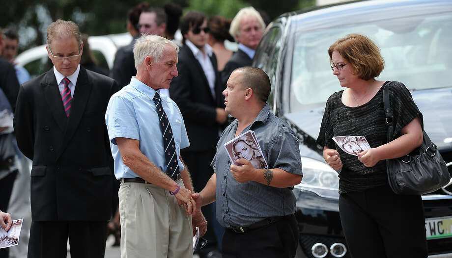 "Mike Steenkamp, the uncle of late South African model Reeva Steenkamp, is comforted by unidentified relatives holding the funeral ceremony program at the crematorium building in Port Elizabeth on February 19, 2013 after Steenkamp, 29, was shot four times in the early hours of February 14, 2013 by a 9mm pistol owned by South African sporting hero Oscar Pistorius. South African prosecutors on Tuesday told a bail hearing that Oscar Pistorius was guilty of ""premeditated murder"" in the Valentine's Day killing of his model girlfriend at his upscale home. Photo: ALEXANDER JOE, AFP/Getty Images / 2013 AFP"