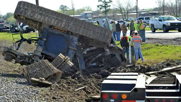 A view of the damaged construction equipment from the crossing where the truck initially got stuck.  The Jefferson County Sheriff's Office and Union Pacific Railroad officials are at the scene of an accident on U.S. 90 in the area of China, where a train struck a loaded  18-wheeler. There is one reported death from the crash and the wreck happened at about 8 a.m. as the 18-wheeler with three construction workers were headed to a job site. The truck's trailer got stuck on the tracks, and two men tried to free the trailer while the third remained in the truck. The train struck the truck, killing one of the men outside the truck. The man inside the truck was taken by medical helicopter to Christus St. Elizabeth Hospital and is currently in critical condition. The third man was not injured.  Attempts to avoid debris in the road by passing vehicles resulted in a second wreck with two other vehicles. There were no injuries from that wreck.    Dave Ryan/The Enterprise