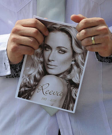 "A relative of the late South African model Reeva Steenkamp holds the funeral ceremony program at the crematorium building in Port Elizabeth on February 19, 2013 after Steenkamp, 29, was shot four times in the early hours of February 14, 2013 by a 9mm pistol owned by South African sporting hero Oscar Pistorius. South African prosecutors on Tuesday told a bail hearing that Oscar Pistorius was guilty of ""premeditated murder"" in the Valentine's Day killing of his model girlfriend at his upscale home. Photo: ALEXANDER JOE, AFP/Getty Images / 2013 AFP"