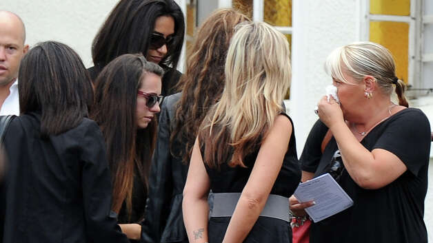 "Relatives and friends of late South African model Reeva Steenkamp gather during the funeral ceremony at the crematorium building in Port Elizabeth on February 19, 2013. The 29-year-old law graduate and cover girl was gunned down four times on February 14, 2013 at the upmarket Pretoria home of the Olympic and Paralympic star Oscar Pistorius. South African prosecutors on February 19 told a bail hearing that Oscar Pistorius was guilty of ""premeditated murder"" in the Valentine's Day killing of his model girlfriend at his upscale home. Photo: ALEXANDER JOE, AFP/Getty Images / 2013 AFP"