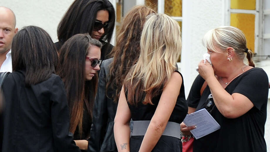 """Relatives and friends of late South African model Reeva Steenkamp gather during the funeral ceremony at the crematorium building in Port Elizabeth on February 19, 2013. The 29-year-old law graduate and cover girl was gunned down four times on February 14, 2013 at the upmarket Pretoria home of the Olympic and Paralympic star Oscar Pistorius. South African prosecutors on February 19 told a bail hearing that Oscar Pistorius was guilty of """"premeditated murder"""" in the Valentine's Day killing of his model girlfriend at his upscale home. Photo: ALEXANDER JOE, AFP/Getty Images / 2013 AFP"""