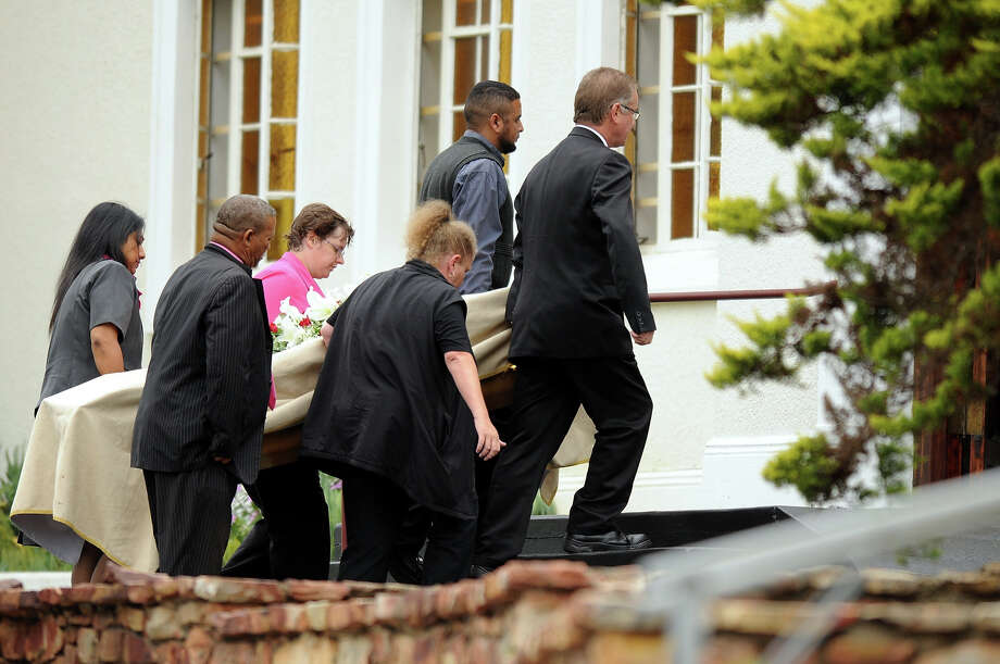 Pallbearers carry in the coffin of the late Reeva Steenkamp on February 19, 2013 in Port Elizabeth, South Africa. Steenkamp was allegedly murdered by boyfriend, Oscar Pistorius on February 14, 2013. Pistorius, who has been charged with the murder, is appearing in court today for his bail hearing. Steenkamp's memorial is being held at The Victoria Park Crematorium. Photo: Gallo Images, Getty Images / 2013 Gallo Images (PTY) LTD