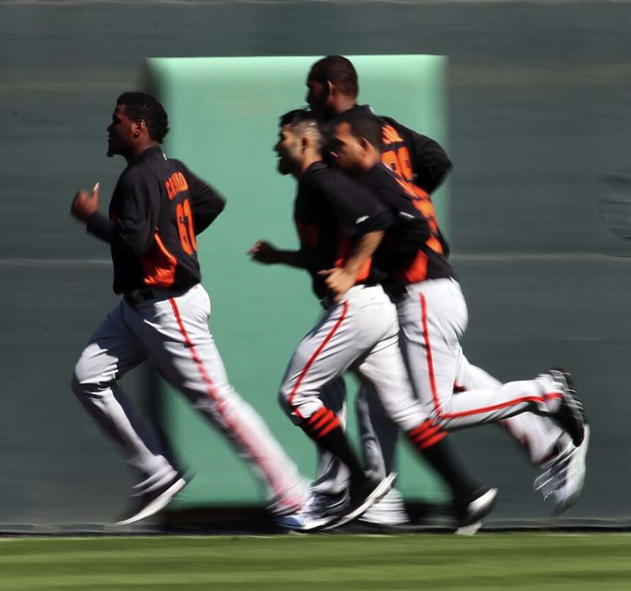 The San Francisco Giants run laps around the practice field at Scottsdale Stadium during warm ups at spring training Monday, Feb. 18, 2013, in Scottsdale, Ariz. Photo: Lance Iversen, The Chronicle / ONLINE_YES