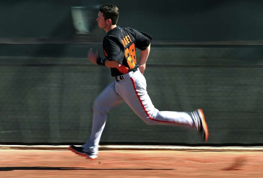 San Francisco Giants' catcher Buster Posey runs wind sprints during spring training Monday, Feb. 18,