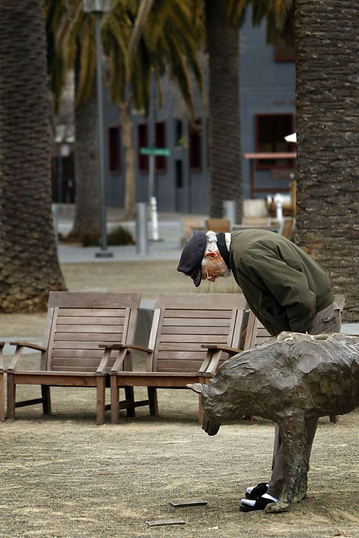 Richard Keup of Livermore, looks at a bronze paw print next to the wolf sculpture in Palm Plaza in Jack London Square in Oakland, Calif., on Monday, February 18, 2013. The space holds several monuments to Jack London, including his cabin and Heinold's First And Last Chance Saloon, where London would spend time when he lived in Oakland.