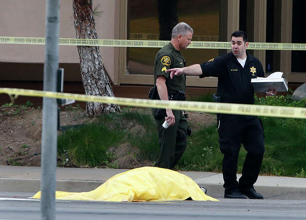 Investigators walk past a tarp covered body in Orange, Calif., Tuesday, Feb. 19, 2013. Police say a chaotic 25-minute shooting spree through Orange County left a trail of dead and injured victims before the shooter killed himself. Orange County sheriff's spokesman Jim Amormino say there are at least six crime scenes with three people, including the suspected gunman, dead and several others wounded. Tustin police Supervisor Dave Kanoti said the shootings started with an apparent carjacking just after 5 a.m. Tuesday in an unincorporated Ladera Ranch area of Orange County. (AP Photo/Jae C. Hong) Photo: Jae C. Hong