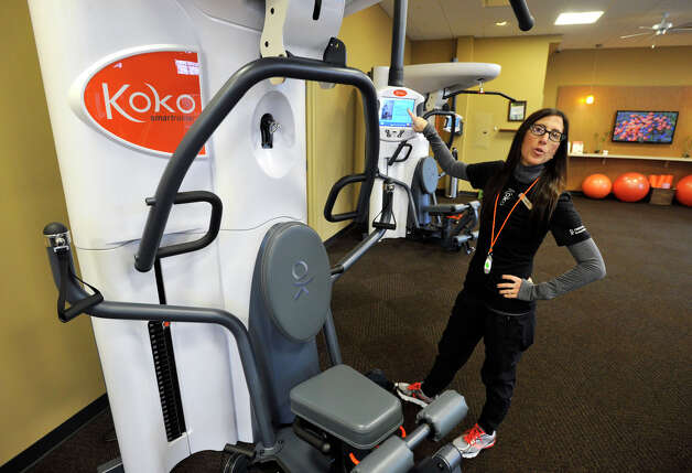 FitCoach Lauren Sugar demonstrates a workout machine at Koko FitClub in Ridgefield on Tuesday, Feb. 19, 2013. The workout facility opened last November. The unique feature of the business is that it uses computers to track your workout routine and charts your progress. Photo: Jason Rearick / The News-Times