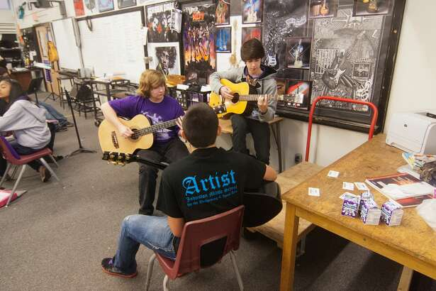 Johnston eighth-graders Sonny Lund, 14, Matthew McCleskey, 14, and Cameron Wieman, 14, practice guitar during class at Johnston Middle School.