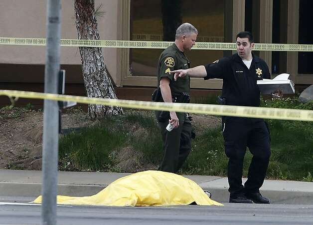 Investigators walk past a tarp covered body in Orange, Calif., Tuesday, Feb. 19, 2013. Police say a chaotic 25-minute shooting spree through Orange County left a trail of dead and injured victims before the shooter killed himself. Orange County sheriff's spokesman Jim Amormino say there are at least six crime scenes with three people, including the suspected gunman, dead and several others wounded. Tustin police Supervisor Dave Kanoti said the shootings started with an apparent carjacking just after 5 a.m. Tuesday in an unincorporated Ladera Ranch area of Orange County. Photo: Jae C. Hong, Associated Press