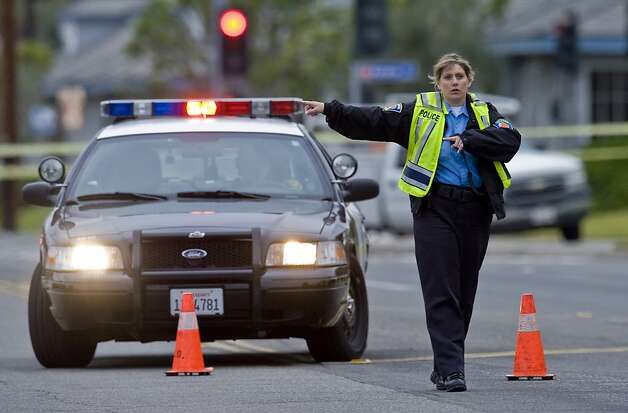 An Orange police officer directs traffic as an investigation of a shooting continues, Tuesday, Feb. 19, 2013 in Orange County, Calif. Police say a chaotic 25-minute shooting spree through Orange County left a trail of dead and injured victims before the shooter killed himself. Orange County sheriff's spokesman Jim Amormino say there are at least six crime scenes with three people, including the suspected gunman, dead and several others wounded. Tustin police Supervisor Dave Kanoti said the shootings started with an apparent carjacking just after 5 a.m. Tuesday in an unincorporated Ladera Ranch area of Orange County. Photo: Mark Rightmire,, Associated Press