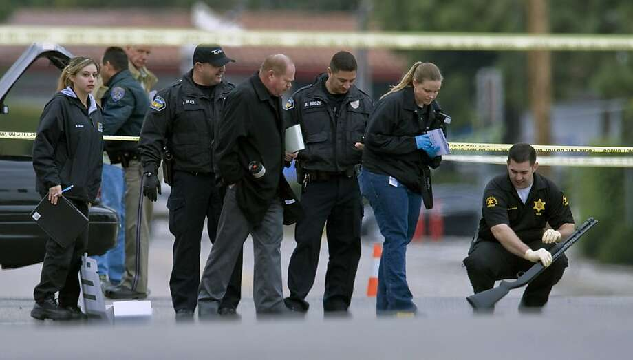 Police investigators examine a gun laying in the street at the intersection of Wanda Road and Katella Avenue in Orange, Calif., Tuesday, Feb. 19, 2013. Police say a chaotic 25-minute shooting spree through Orange County left a trail of dead and injured victims before the shooter killed himself. Orange County sheriff's spokesman Jim Amormino say there are at least six crime scenes with three people, including the suspected gunman, dead and several others wounded. Tustin police Supervisor Dave Kanoti said the shootings started with an apparent carjacking just after 5 a.m. Tuesday in an unincorporated Ladera Ranch area of Orange County. Photo: Mark Rightmire,, Associated Press