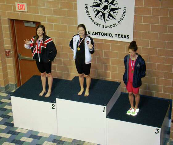 "Judson's Ashley Wayman, center, gives the ""Diamond J"" salute during the awards ceremony last week, after she took first place in the 100 backstroke during the Class 5A regional swim meet. Photo: Courtesy Photo"