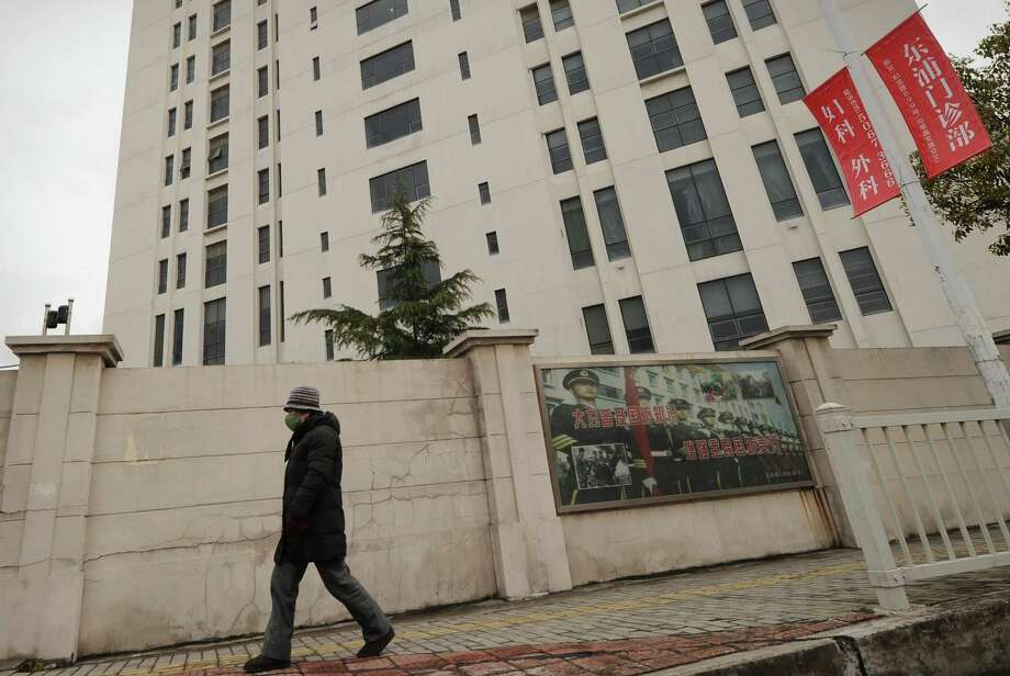 A person walks past a 12-story building in Shanghai alleged in a report by Internet security firm Mandiant as the home of a Chinese military-led hacking group after the firm reportedly traced a host of cyberattacks to it. Photo: PETER PARKS, Staff / AFP