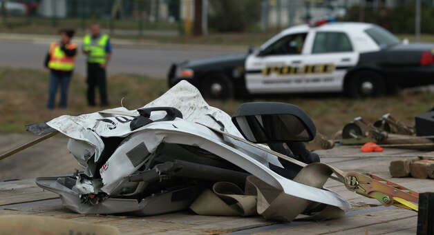 The crumpled door of a white pickup truck is strapped to a flatbed trailer Tuesday February 19, 2013 at the intersection of Hausman Road and Loop 1604 where an accident took the life of a Brandeis High School student who was allegedly involved in a drag race. The wreck took place about 11:45 a.m. and officer Matthew Porter with the San Antonio Police Department confirmed that a female student died shortly after the crash, but no other information about her was available immediately. Photo: JOHN DAVENPORT, San Antonio Express-News / ©San Antonio Express-News/Photo Can Be Sold to the Public