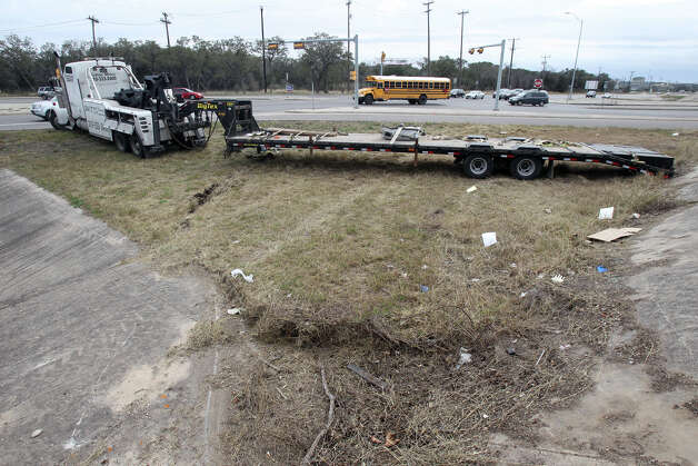 A trailer is about to be hauled off Tuesday February 19, 2013 at the intersection of Hausman Road and Loop 1604 where a traffic accident took the life of a Brandeis High School student allegedly involved in a drag race. The wreck occurred about 11:45 a.m. and Officer Matthew Porter with the San Antonio Police Department confirmed that a female student died shortly after the crash, but no other information about her was available immediately. Photo: JOHN DAVENPORT, San Antonio Express-News / ©San Antonio Express-News/Photo Can Be Sold to the Public