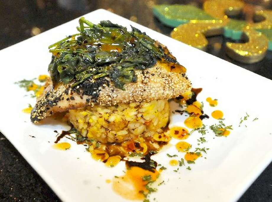 This dinner plate is black and white sesame seed crusted salmon over a shrimp fried rice cake with sweet and spicy spinach.