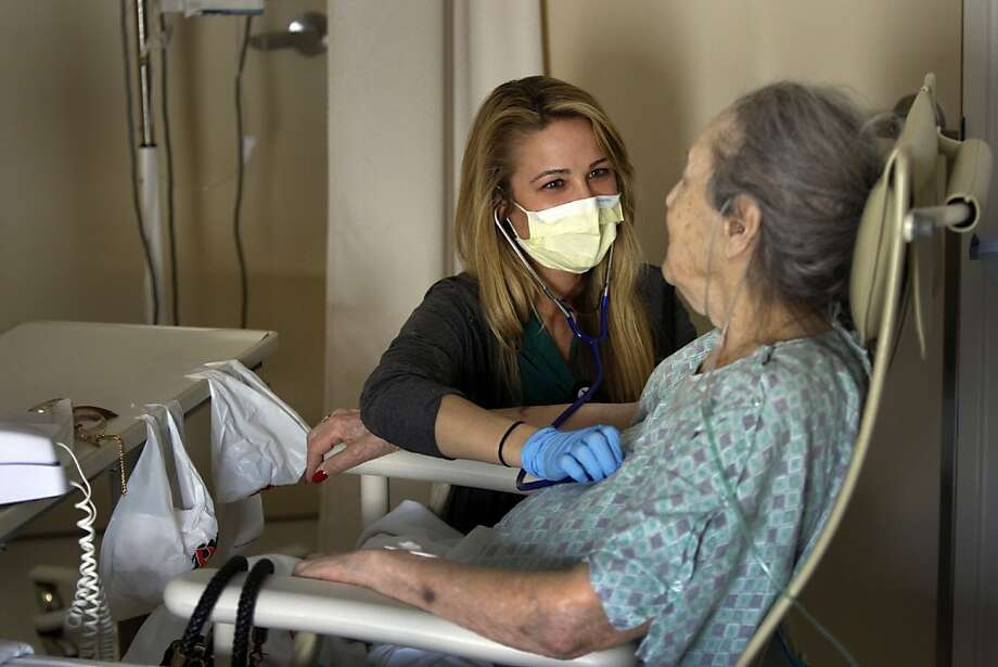 Nurse Jacquelyn Maxton listens to the breathing of Claire Gordon, admitted with pneumonia and the flu. Photo: Allen J. Schaben, McClatchy-Tribune News Service