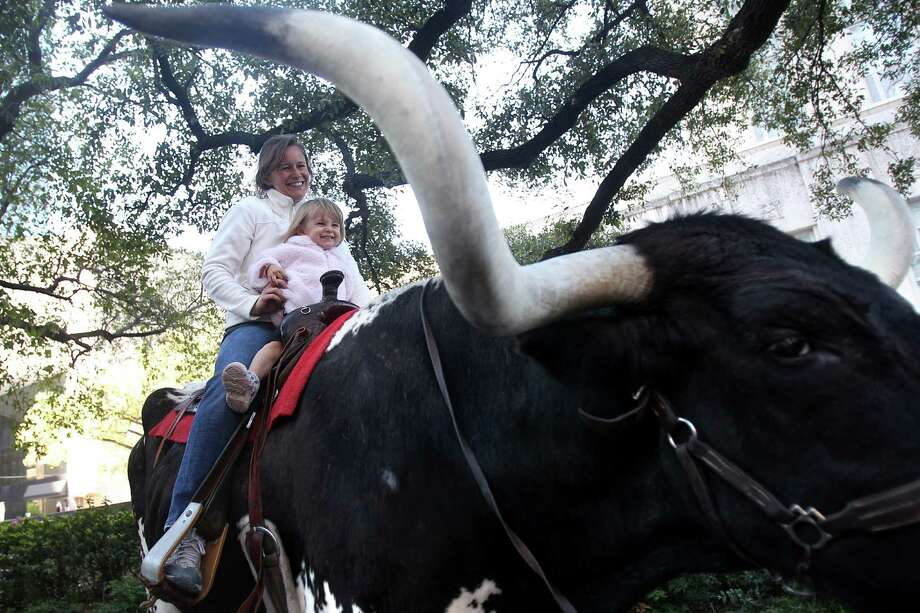 Jessica Herum holds daughter Juliet Herum, 2, while posing for a photo with 2,300 pound 'Hot Shot' during the 2013 Houston Rodeo Roundup where the Houston Livestock Show and Rodeo kicks-off the 2013 rodeo season at City Hall on Tuesday, Feb. 19, 2013, in Houston.  The Rodeo Roundup promotes Houston's rich Western heritage. Photo: Mayra Beltran, Houston Chronicle / © 2013 Houston Chronicle