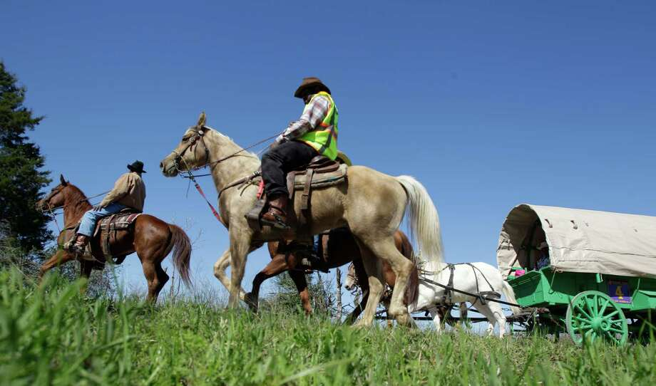 Prairie View Trail Riders move along Reinke Road near FM 362 Tuesday, Feb. 19, 2013, in Hockley.As part of the Houston Livestock Show and Rodeo, riders from 13 different trail rides will arrive in Houston on Friday at Memorial Park and then participate in the Downtown Rodeo Parade on Saturday. Photo: Melissa Phillip, Houston Chronicle / © 2013  Houston Chronicle