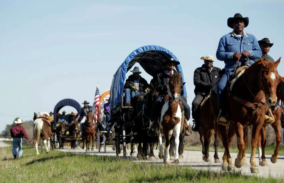 Prairie View Trail Riders move along Owens Road near FM 362 Tuesday, Feb. 19, 2013, in Hockley. As part of the Houston Livestock Show and Rodeo, riders from 13 different trail rides will arrive in Houston on Friday at Memorial Park and then participate in the Downtown Rodeo Parade on Saturday. Photo: Melissa Phillip, Houston Chronicle / © 2013  Houston Chronicle
