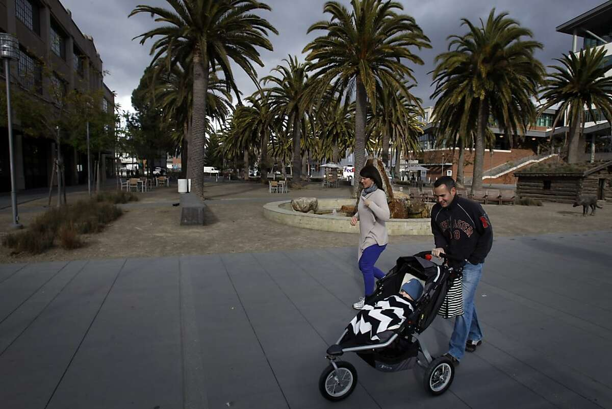 Pedestrians walk by Palm Plaza in Jack London Square at the end of Webster Street in Oakland, Calif., on Monday, February 18, 2013. The space holds several monuments to Jack London, including his cabin and Heinold's First And Last Chance Saloon, where London would spend time when he lived in Oakland.
