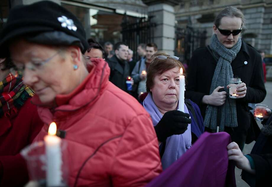 Relatives of victims of the Magdalene Laundries hold a candlelit vigil before Prime Minister Enda Kenny's apology. Photo: Peter Morrison, Associated Press