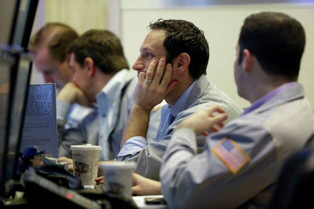 Traders work on the floor at the New York Stock Exchange in New York, Tuesday, Feb. 19, 2013. Talk of more mergers and acquisitions is sending stock prices slightly higher in early trading, setting the market up to continue a seven-week rally.  (AP Photo/Seth Wenig) Photo: Seth Wenig