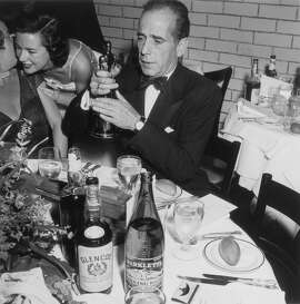20th March 1952:  EXCLUSIVE American actor Humphrey Bogart (1899 - 1957) sits at a table with place settings and liquor bottles, holding up his Best Actor statue at the Academy Awards, RKO Pantages Theater, Los Angeles, California. Bogart won the Oscar for his role in director John Huston's film, 'The African Queen.'  (Photo by Murray Garrett/Getty Images)