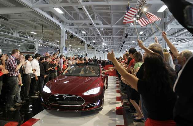 Tesla workers cheer at the factory in Fremont when one of the first Model S sedans was sold last June. Photo: Paul Sakuma, Associated Press