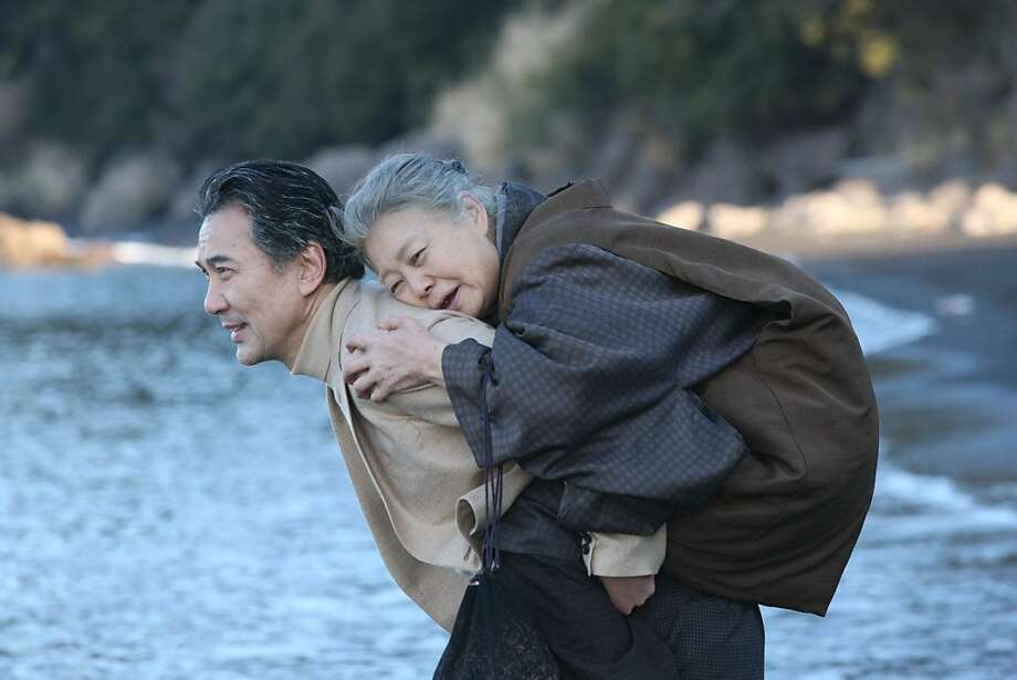 "Kosaku (Koji Yakusho) carries his mother (Kirin Kiki) on his back - literally and figuratively - in Masato Harada's film ""Chronicle of My Mother."" Photo: Lamorinda Film"
