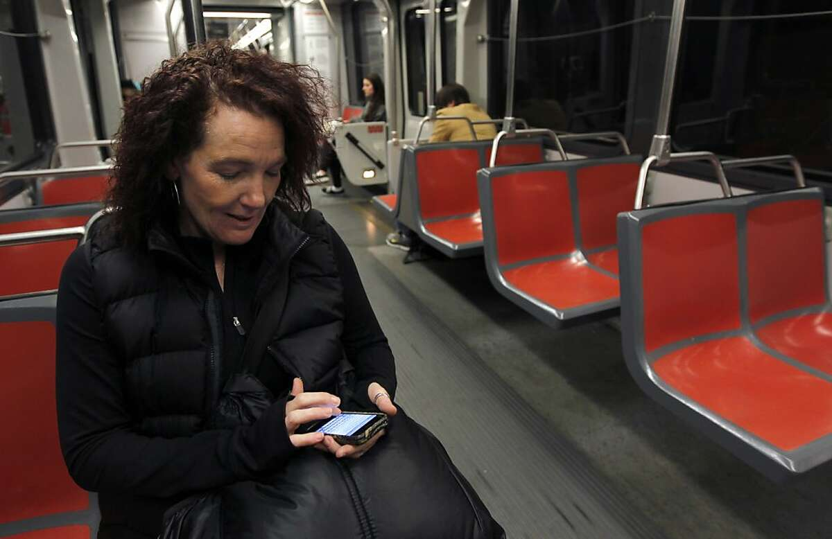 Stacey Lonegan taps out an email on her cell phone while riding on a Muni Metro train between the Powell and Montgomery stations in San Francisco, Calif. on Monday, Feb. 18, 2013. Lonegan said she'll wait to send it when she'll regain cellular coverage. Cellular service is still spotty in many sections of the transit system's network of underground tunnels and stations.