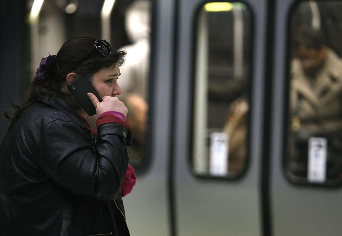 A passenger, who said her name is Jocelyn, talks on a cell phone while waiting to board a Muni Metro train at the Embarcadero station in San Francisco, Calif. on Monday, Feb. 18, 2013. Cellular service is still spotty in many sections of the transit system's network of underground tunnels and stations.