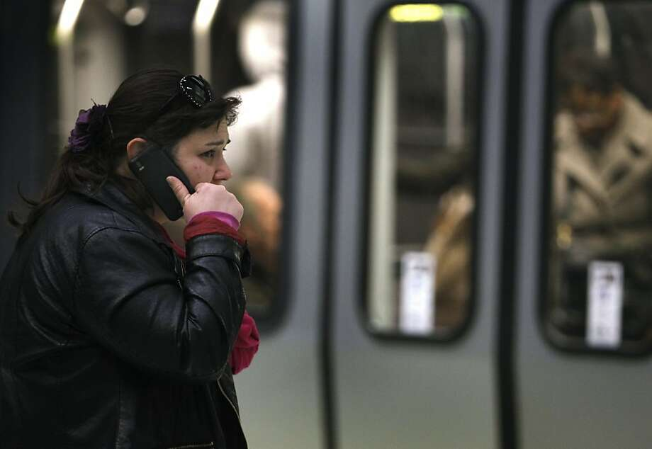 A passenger, who said her name is Jocelyn, talks on a cell phone while waiting to board a Muni Metro train at the Embarcadero station in San Francisco, Calif. on Monday, Feb. 18, 2013. Cellular service is still spotty in many sections of the transit system's network of underground tunnels and stations. Photo: Paul Chinn, The Chronicle