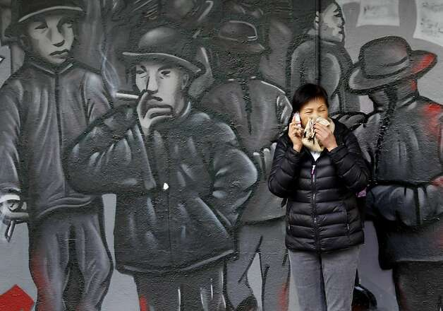 In Chinatown, a woman wiped her nose as she stood near a mural at Clay and Grant Streets in San Francisco, Calif. A day of cold rain turned into a day of cold wind Tuesday February 19, 2013 across the Bay Area. Photo: Brant Ward, The Chronicle