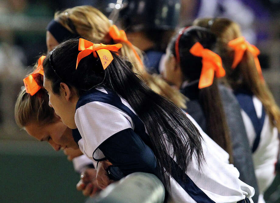 Brandeis softball players wear orange ribbons with the initials of former teammate Gabriella Lerma during a game against O'Connor High School to remember Lerma who died in a drag racing incident on Tuesday, Feb. 19, 2013. Lerma was a junior at Brandeis. Photo: Kin Man Hui, San Antonio Express-News / © 2012 San Antonio Express-News
