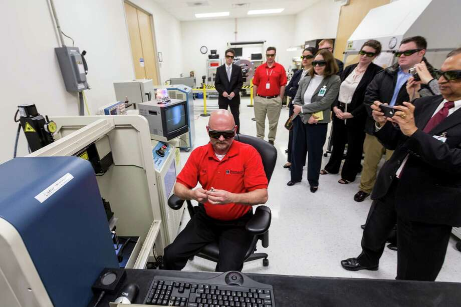Bill Gibler uses a laser to weld a pressure and temperature sensor for well applications as oil services giant Halliburton highlighted its technology Tuesday at its Fiber Optic Center in Houston. during a tour of Halliburton's Fiber Optics Facility at Pinnacle, a Halliburton Service, Tuesday, Feb. 19, 2013, in Houston. ( Michael Paulsen / Houston Chronicle ) Photo: Michael Paulsen, Staff / © 2013 Houston Chronicle