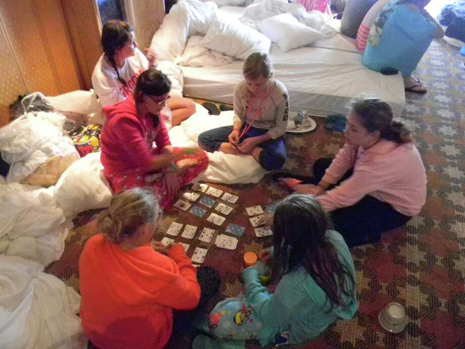 Sisters Amber Brown, 11, Elyse Brown, 9, and Macy Ray, 12, play cards with other children stranded on the Carnival Triumph last week after an engine room fire disabled the cruise ship. Photo: Courtesy Of The Brown Family