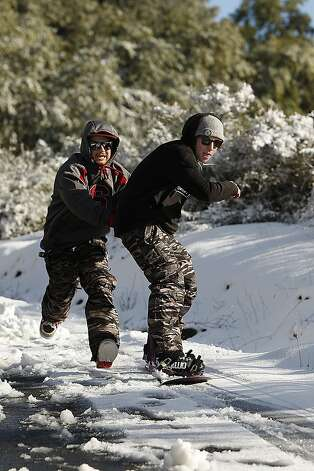 Concord resident, Woody Wilcox gets a push from Shane White, also of Concord, as they take advantage of the snowfall at Mount Diablo State Park and snowboard on February 19, 2013 in Clayton, Calif. Heavy rains and cold temperatures around the Bay Area brought snow to the higher elevation of Mount Diablo SP. Photo: Sean Havey, The Chronicle