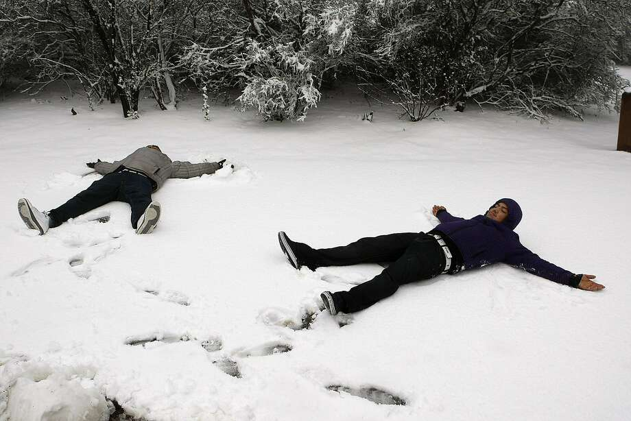 Yovanhi Hernandez, left, and Luciano Lopez make snow angels on Mount Diablo State Park on February 19, 2013 in Clayton, Calif. Heavy rains and cold temperatures around the Bay Area brought snow to the higher elevation of Mount Diablo SP. Photo: Sean Havey, The Chronicle