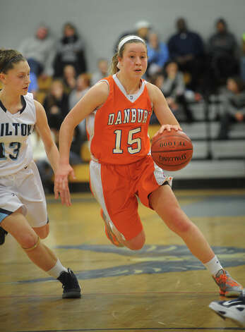 Danbury's Rebecca Gartner drives the ball to the basket ahead of Wilton's Erica Mckenna Pearsall during the FCIAC girls' basketball semi-finals at Ludlowe High School in Fairfield on Tuesday, February 19, 2013. Photo: Brian A. Pounds / Connecticut Post