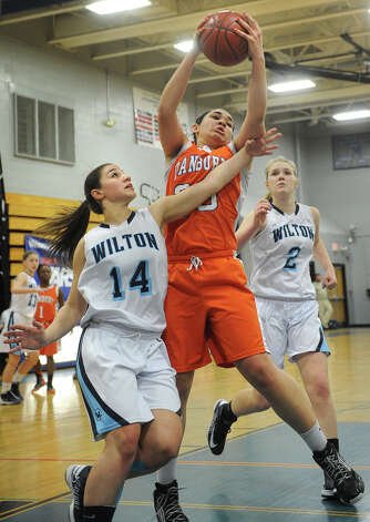 Wilton's Alyssa Malvarosa, left, and Erin Cunningham defend Danbury's Kayla Handberry during the FCIAC girls' basketball semi-finals at Ludlowe High School in Fairfield on Tuesday, February 19, 2013. Photo: Brian A. Pounds / Connecticut Post