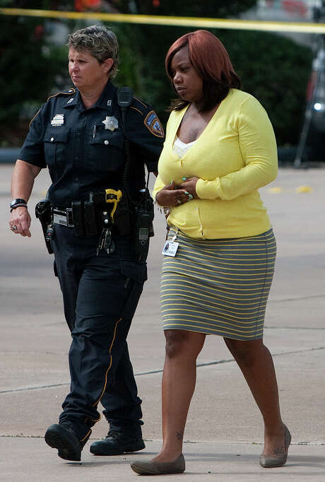 A Harris County sheriff's deputy escorts Crystal Scott after the fatal shooting of Jonathan Ables at a gas station in northwest Houston on Sept. 17, 2012. Photo: Cody Duty, Staff / © 2012 Houston Chronicle