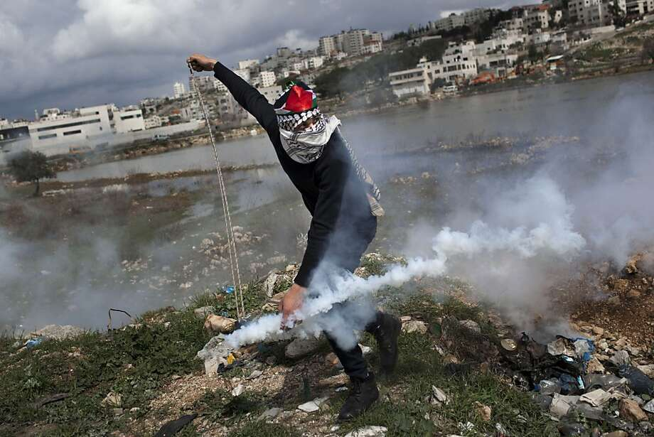 A masked Palestinian throws back a gas canister previously shoot by Israeli forces, not pictured, during a protest to support Palestinian prisoners, outside Ofer, an Israeli military prison near the West Bank city of Ramallah, Tuesday, Feb. 19, 2013. Palestinian protesters clashed with Israeli soldiers at a rally Tuesday in support of four imprisoned Palestinians on hunger strike, as hundreds of inmates said they were refusing food for the day in solidarity with the fasting inmates. One of the four hunger-striking Palestinians is 35-year-old Samer Issawi whose health has severely deteriorated after he has refused food, on-and-off, for more than 200 days.  Photo: Bernat Armangue, Associated Press
