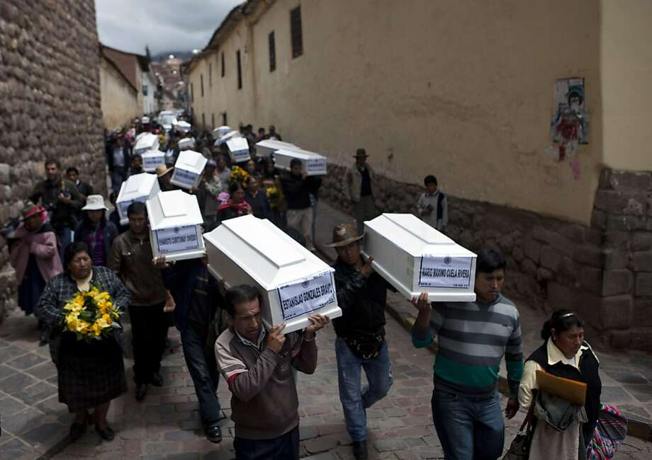 People carry coffins containing the remains of people whose bodies were excavated, to a church in Cuzco, Peru, Tuesday, Feb. 19, 2013. Authorities turned over to families 26 coffins containing the remains of people from various towns whose body parts were excavated from 250 graves since November. According to Peruvian authorities, the victims, including women, children and village authorities, were killed by both members of the Shining Path militant group and the army between 1980 and 2000, and are among tens of thousands of Peruvians who died during the Maoist-inspired insurgency. Photo: Martin Mejia, Associated Press