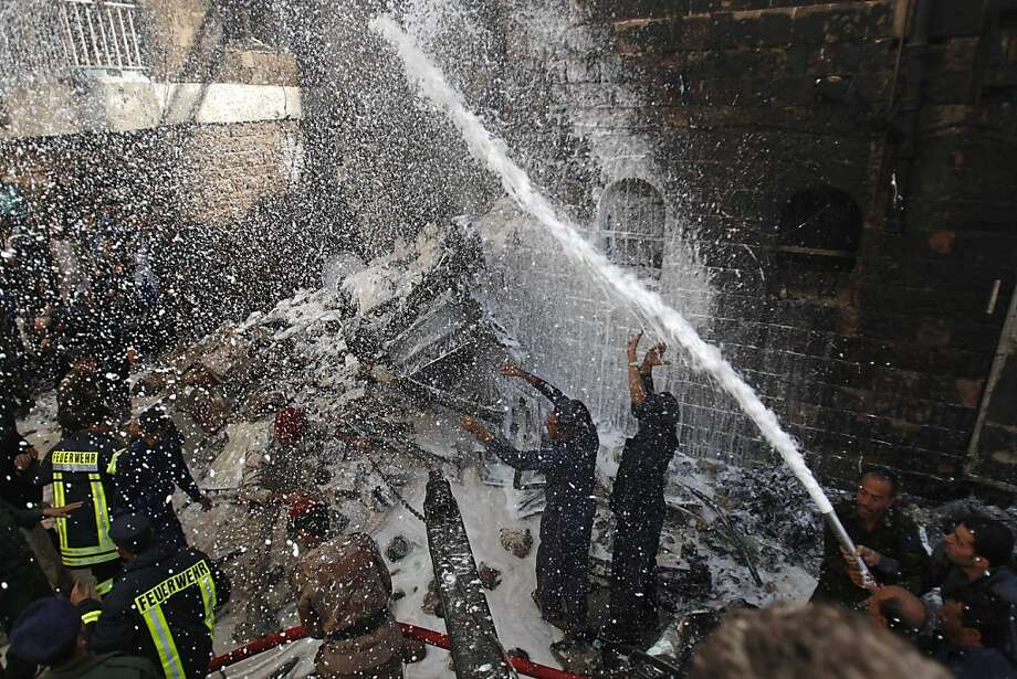 Yemeni soldiers and firefighters work to extinguish fire at the site of a plane crash in Sanaa, Yemen, Tuesday, Feb. 19, 2013. A Yemeni official says a military plane on a training exercise crashed into a neighborhood in the country's capital, Sanaa, killing and injuring scores of people. Photo: Hani Mohammed, Associated Press