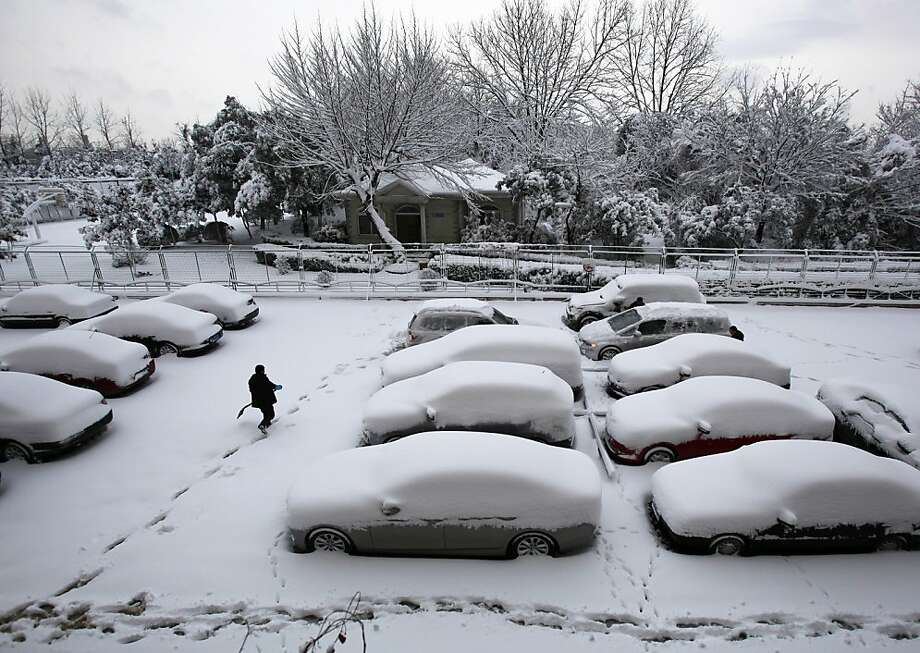 A man carries a shovel while walking past snow covered vehicles at a parking lot after a snow fall in Nanjing in east China's Jiangsu province Tuesday, Feb. 19, 2013. Photo: Associated Press